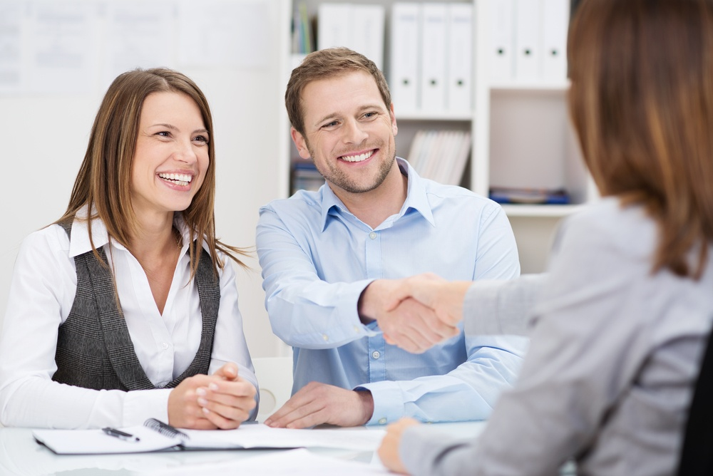 Smiling young man shaking hands with an insurance agent or investment adviser as he sits in a meeting with his wife in her office